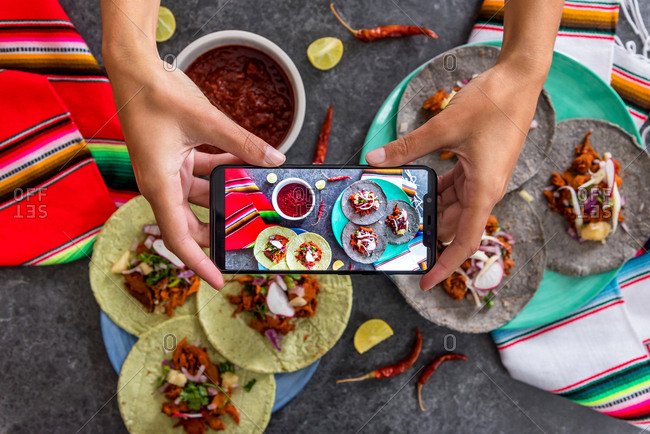 Person photographing Mexican food arrangement on a table