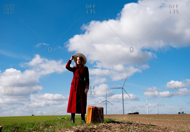 Woman in red coat with suitcase on field with wind turbines