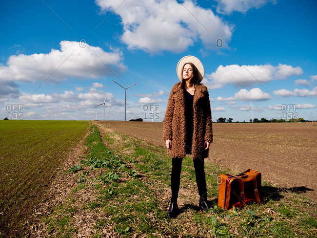 Woman in coat with suitcase on field with wind turbines