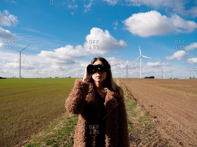 Woman in coat with binocular on field with wind turbines