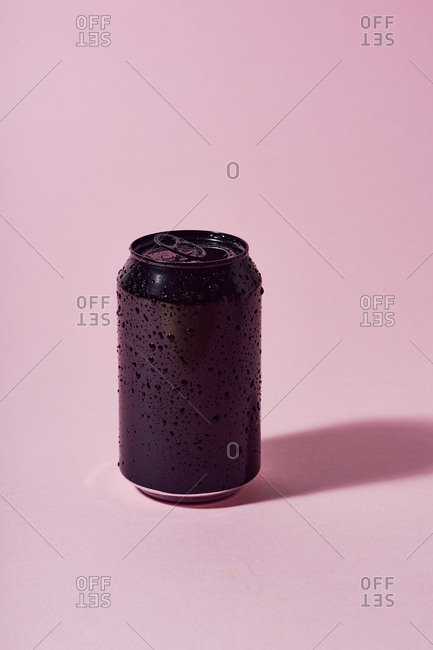 Black wet aluminum beer can on pink background