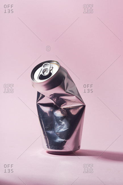 Smashed empty aluminum beer can on pink background
