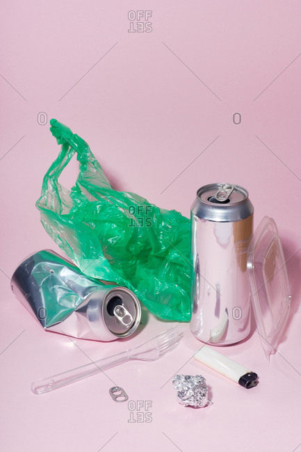 Still life with beer cans and plastic waste on pink background