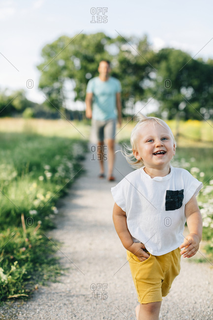 Toddler walking with father - Offset