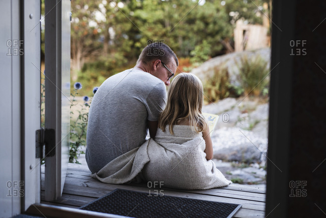 Father and daughter sitting at doorstep