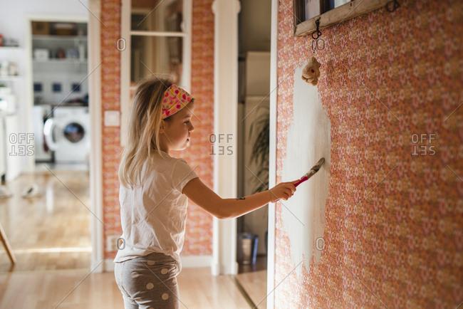 Girl scraping wallpaper