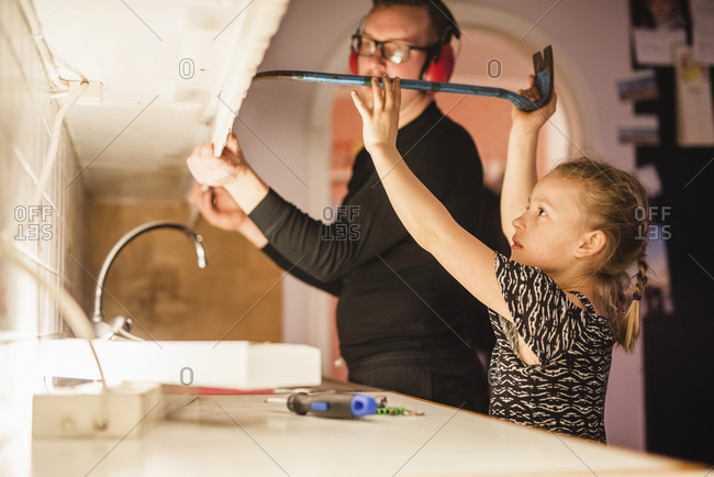 Father and daughter disassembling cupboards