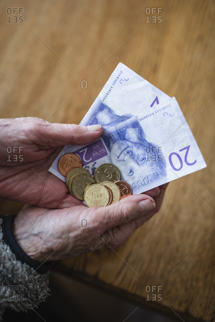 Hands holding banknotes and coins