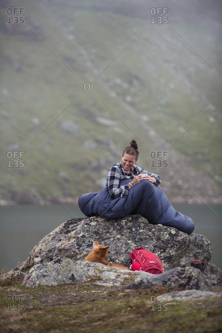 Woman in sleeping bag at lake
