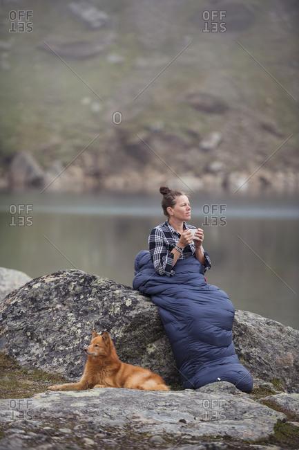 Woman having coffee in sleeping bag