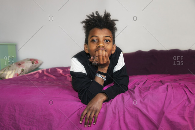 Boy on bed looking at camera