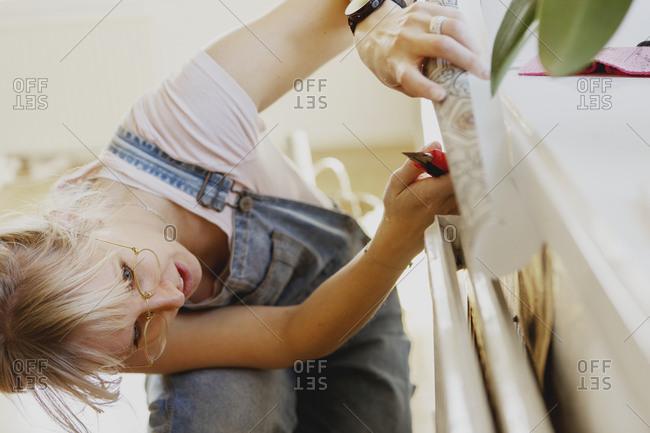 Woman sticking wallpaper on wall