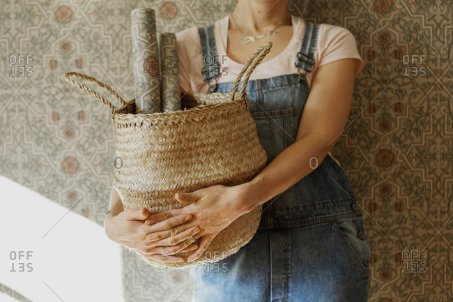 Woman holding basket with wallpaper rolls