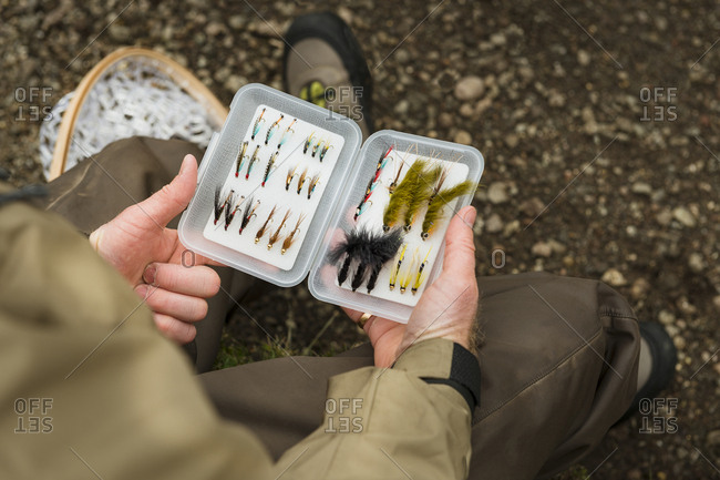 Angler holding with box with fishing flies