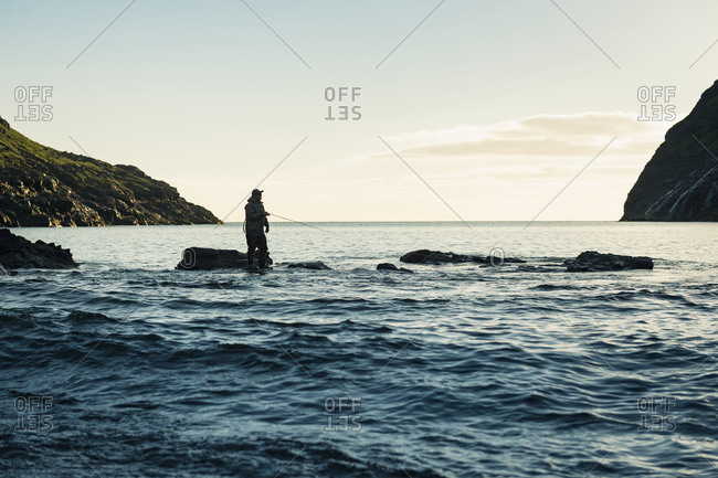Person fishing with pole in water