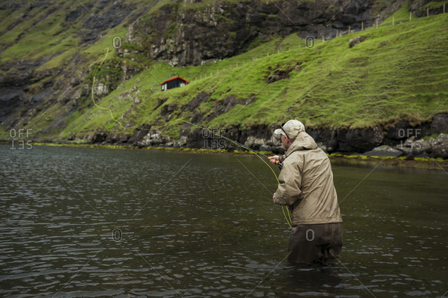 Man fishing with pole in water