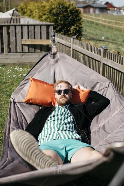 Man relaxing on hammock - Offset