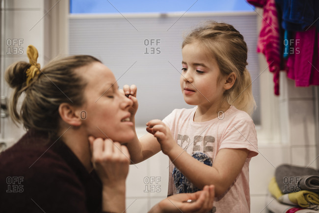 Girl putting make-up on mothers face