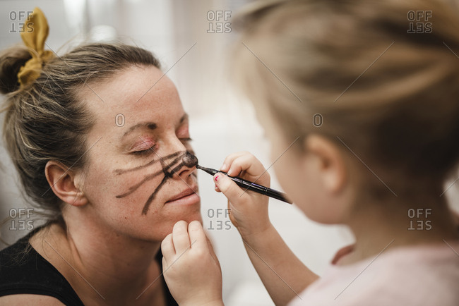 Girl painting mothers face