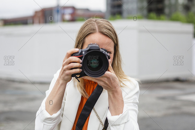 Woman photographing, taking different shots with her camera