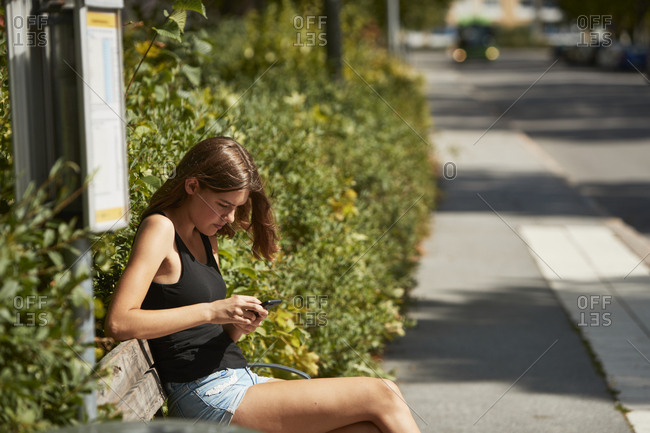Woman sitting on bus stop