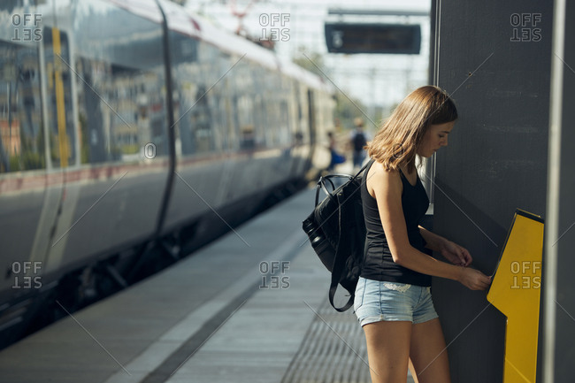 Woman buying ticket on train platform