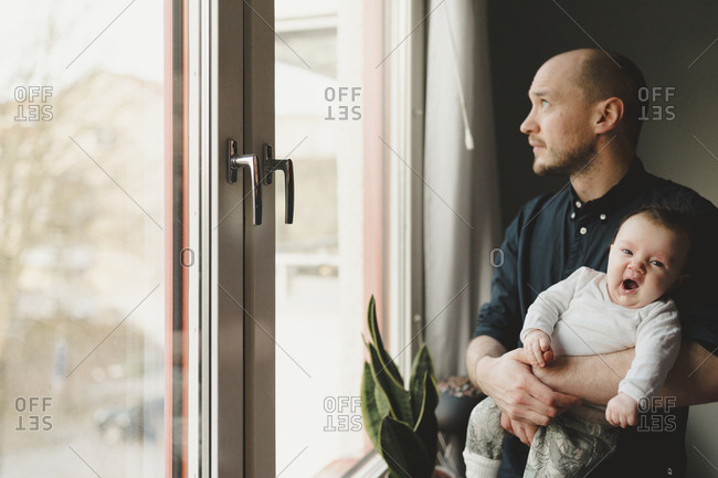 Father with baby looking through window