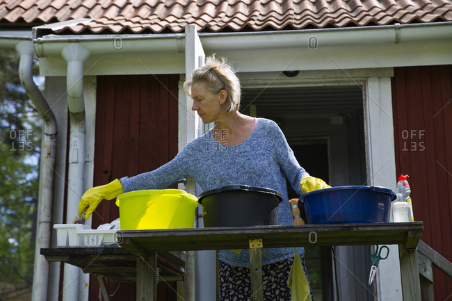 Woman washing dishes in garden
