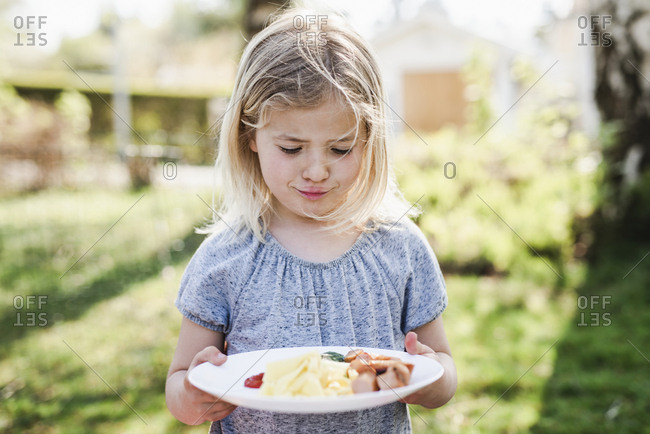 Girl looking at food on her plate
