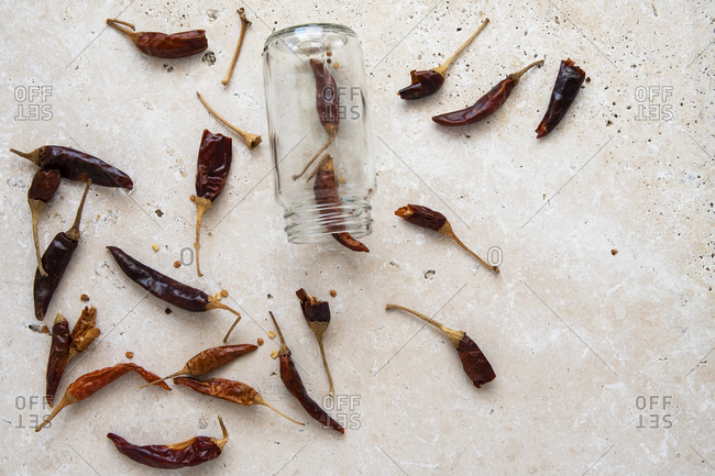 Dried whole chillies out of a herb jar on marble bench top