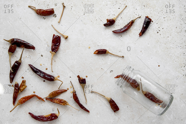 Dried chilli peppers out of a herb glass jar on white marble stone background