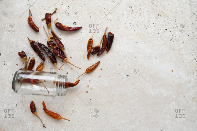 Dried whole chillies out of a small glass jar on white marble stone bench top