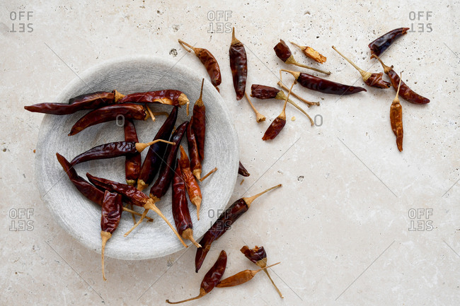 Dried chilli peppers in a handmade stone bowl on white marble bench top