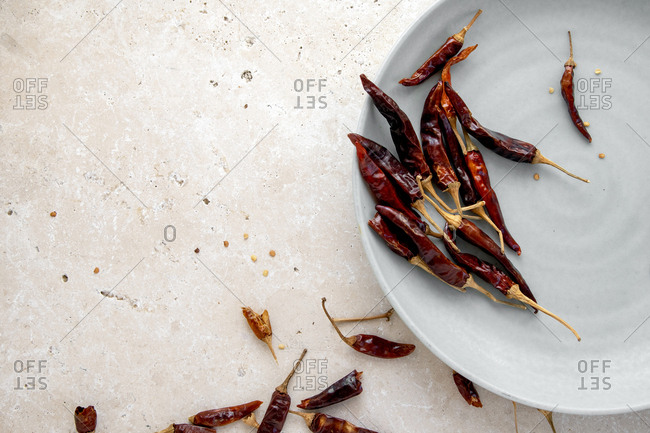 Dried chilli peppers in a ceramic plate on white marble bench top