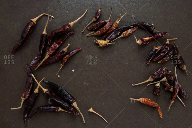 Loose scattered dried chilli peppers on rustic dark brown worn tray