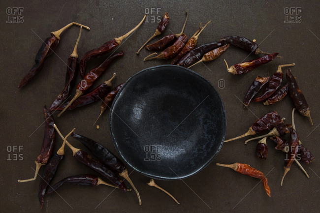 Loose scattered dried chilli peppers around empty spice bowl on rustic tray