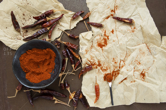 Cayenne and paprika powder in rustic old bowl circled by dried peppers on parchment paper