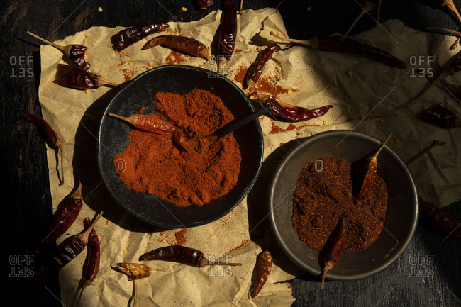 Artistic still life bowls with spice powder and dried chilly peppers