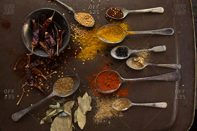 Creative composition of old spoons, herbs and spices