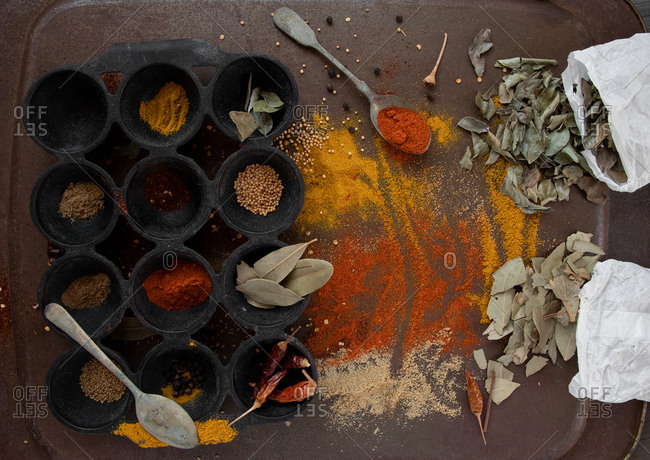 Vibrant colourful arrangement of herb leaves and spices on vintage tray