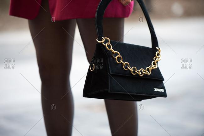 September 14, 2019 - London: Chic Parisian woman holding black Jacquemus handbag