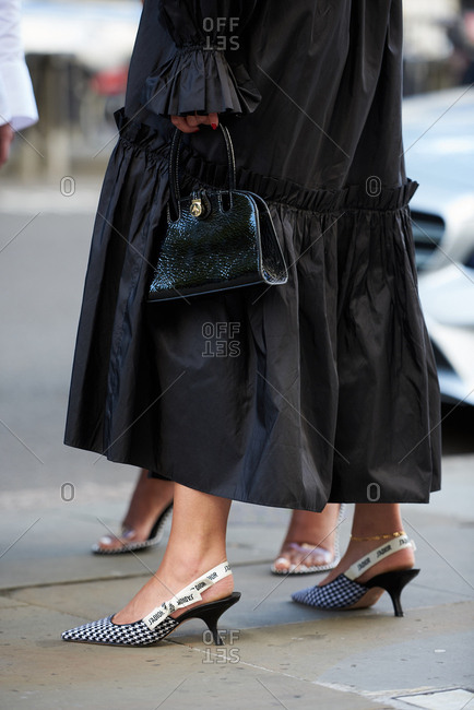 September 14, 2019 - London: Chic woman with black ruffle dress wearing Christian Dior slider heeled pumps