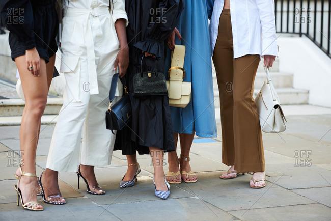 September 14, 2019 - London: Group of stylish fashion influencers pose, wearing designer goods