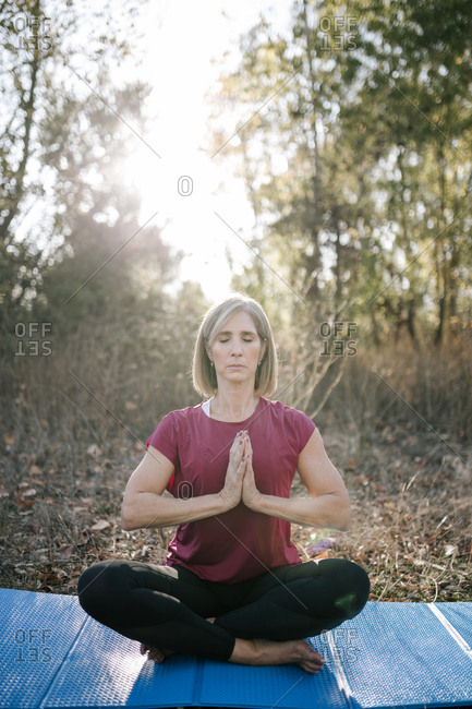 Mature woman doing yoga in a forest