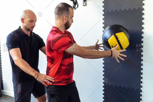 Shot of muscular young man exercising with medicine ball while the instructor corrects his position at the crossfit gym.