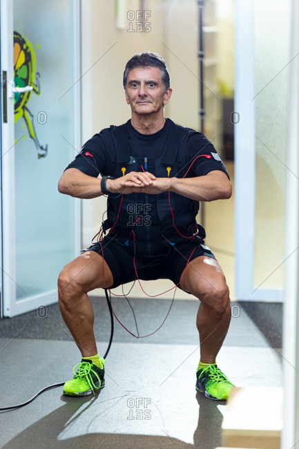 Shot of fitness athletic man in electrical muscle stimulation suit doing squats in the rehabilitation center.