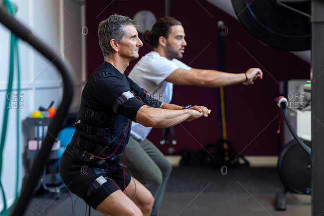 Shot of fitness athletic man in electrical muscle stimulation suit doing squats with instructor in the rehabilitation center.