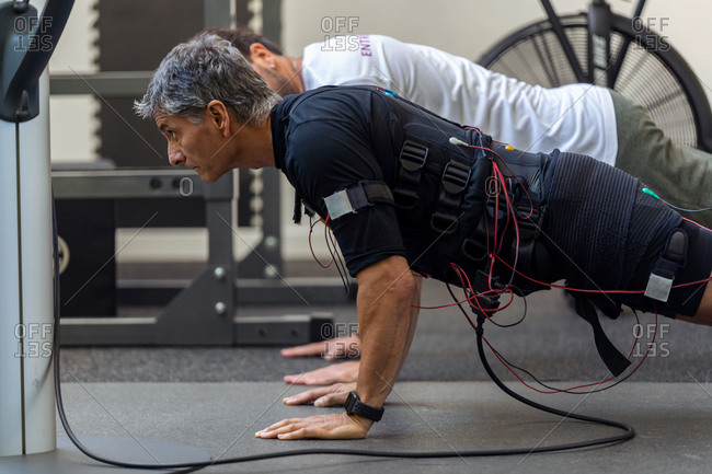 Shot of fitness athletic man in electrical muscle stimulation suit doing plank exercise with instructor in the rehabilitation center.