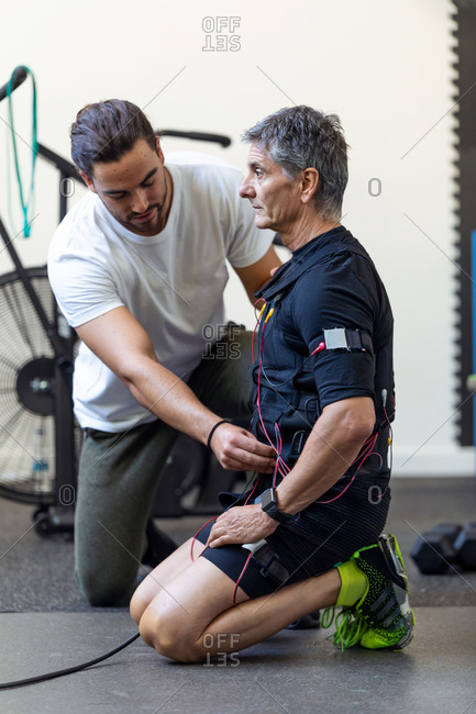 Shot of personal trainer preparing a man to doing exercises with electrical muscle stimulation suit in the rehabilitation center.