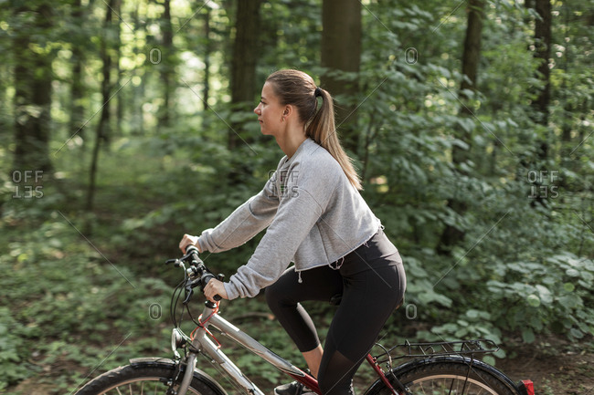 Portrait of a young woman with bike in the forest, Minks, Belarus.